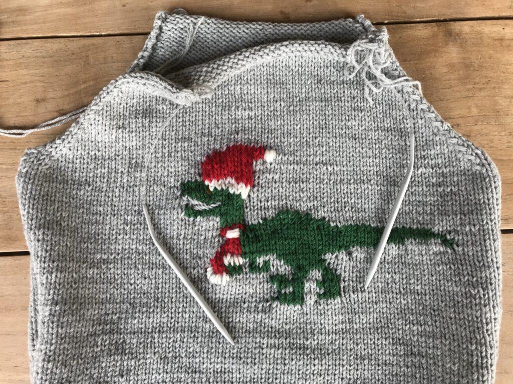 Weihnachtspullover im Raglan -Schnitt mit Baby velociraptor